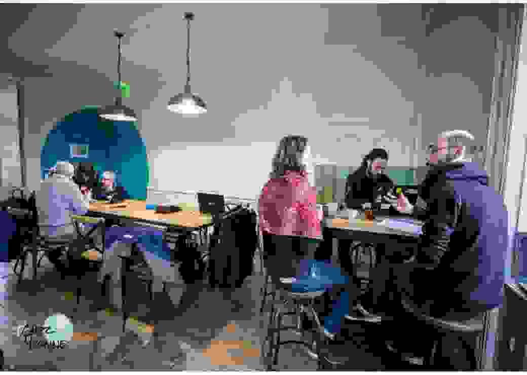 Six personnes sont assises devant des tables, certaines discutent, d'autres travaillent sur des ordinateurs
