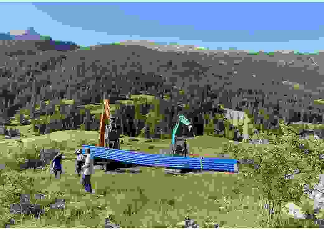 Sur des collines, deux tractopelles décharges un lot de tuyaux
