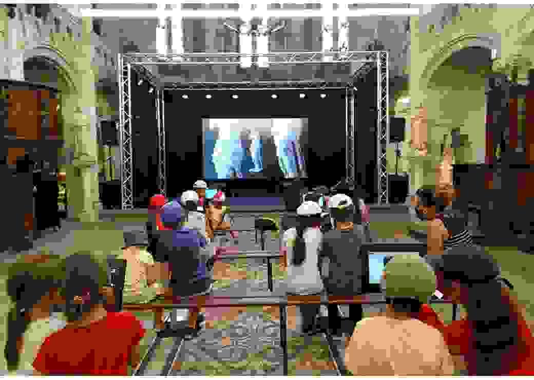 À l'intérieur d'un bâtiment religieux, des enfants regardent sur grand écran des photos d'oeuvres d'art