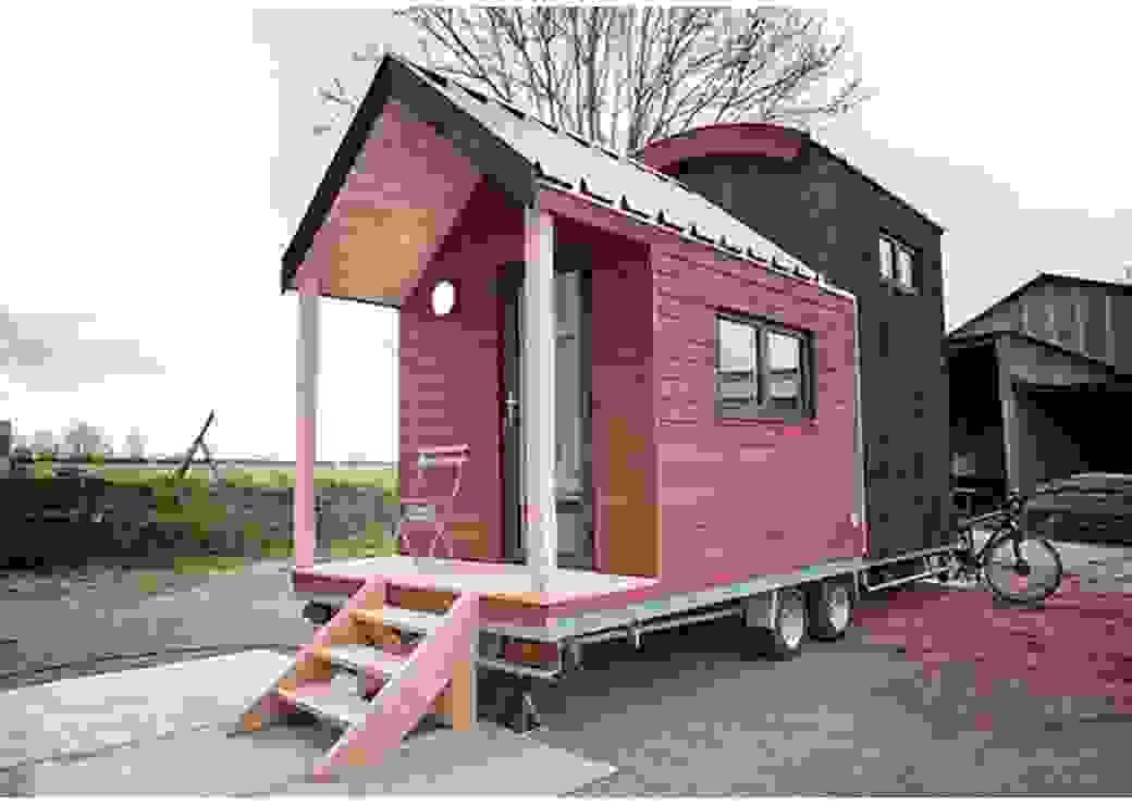 Sur un sol en terre battue, une petite maison de bois, montée sur roues, est installée