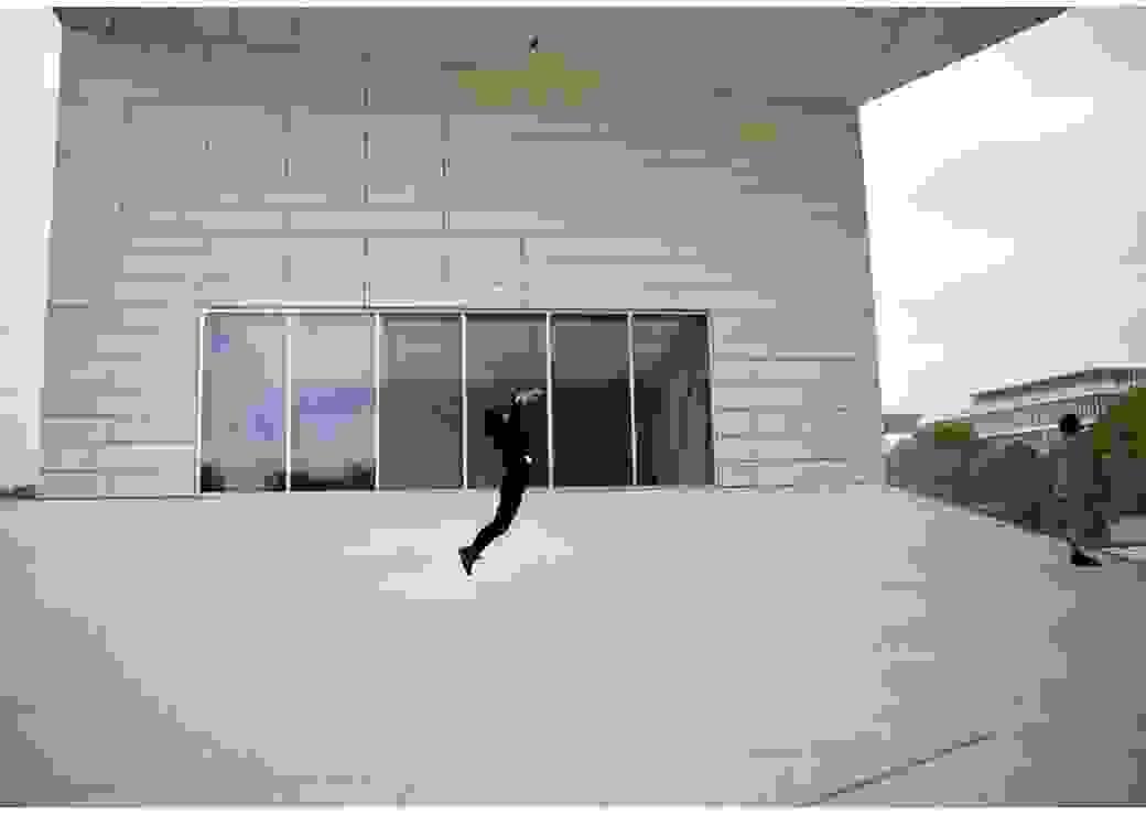 Sur le parvis d'un bâtiment moderne, une personne s'élance dans un saut les bras vers le ciel