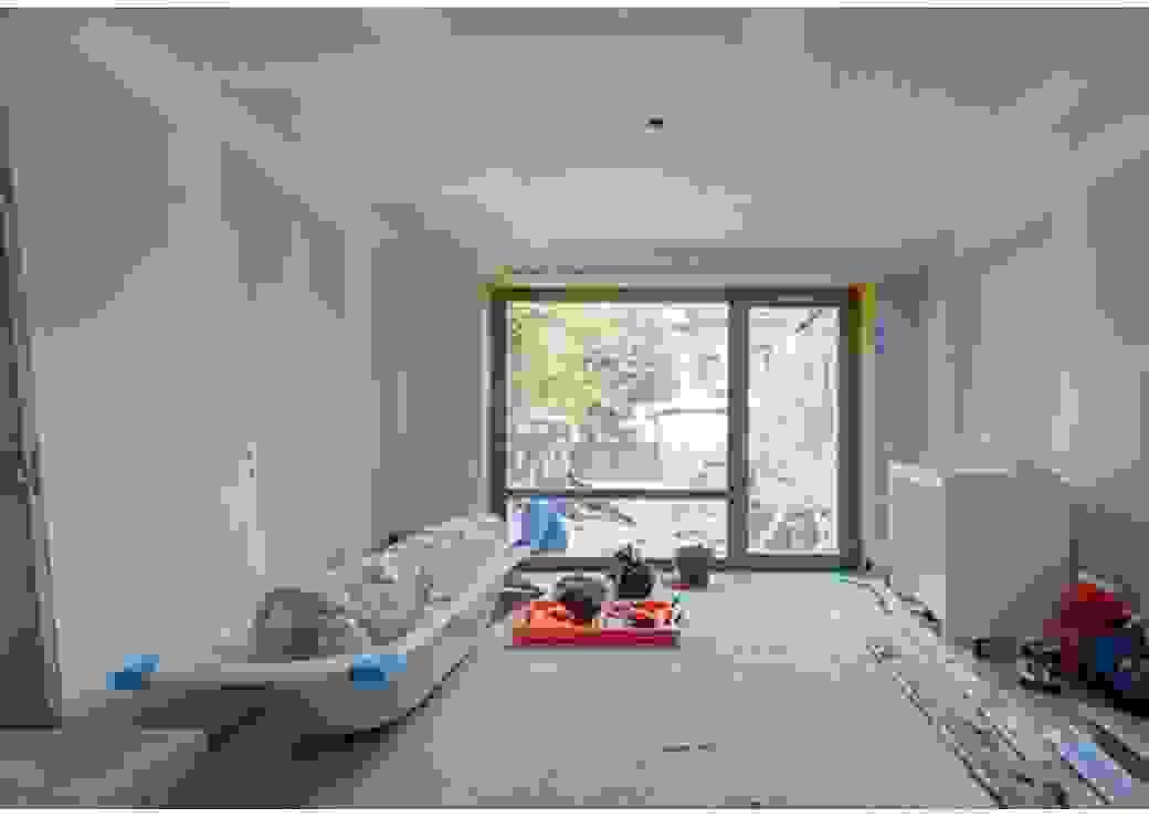Depuis l'entrée de la pièce, vue d'un intérieur dont les murs et les plafonds sont recouverts de plaques de placoplâtre. Au fond, une baie vitrée donne sur une cour intérieure.