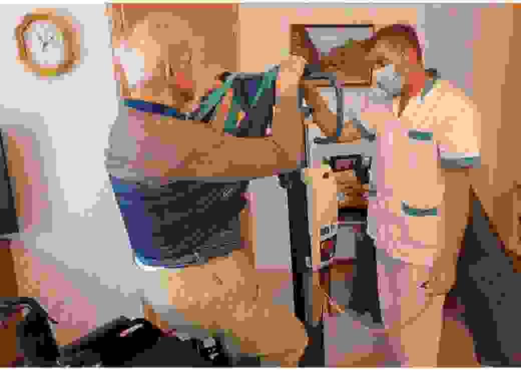 Un homme en habits de soin s'occupe d'un vieil homme dans une chambre où apparaissent des équipement médicaux