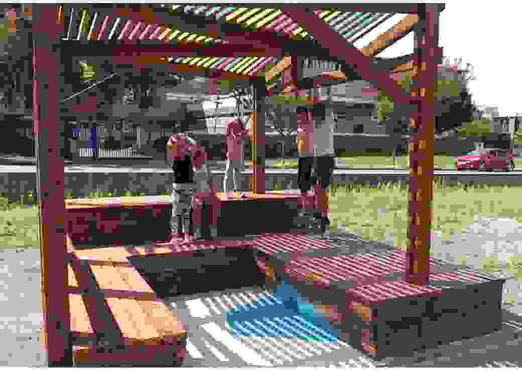 Des enfants jouent sous une ombrière au toit coloré