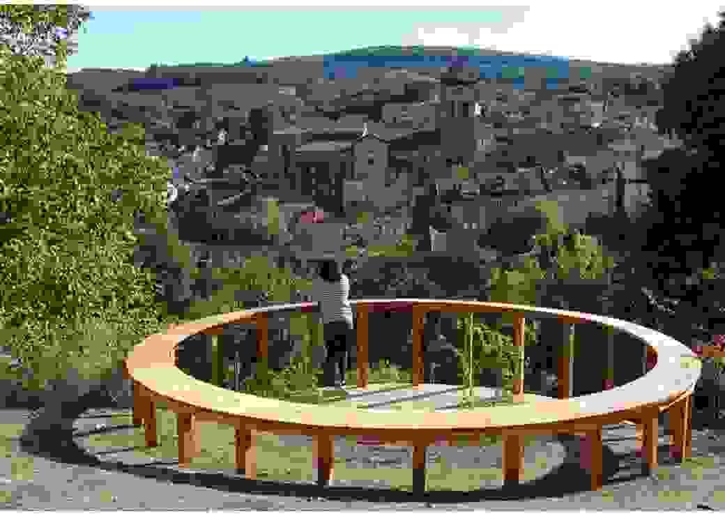 Sur une colline, une personne est appuyée à une construction en bois circulaire et regarde le village situé sur la colline opposée