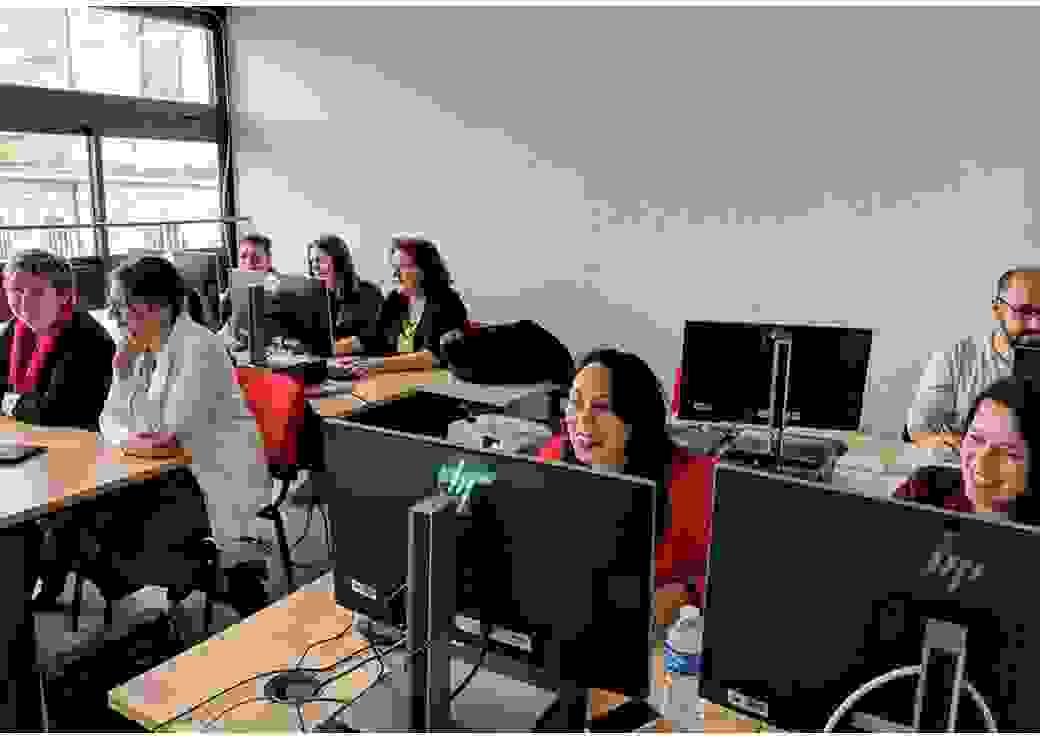 Dans une salle de classe, 8 adultes, principalement des femmes, sont attablés devant des écrans d'ordinateurs