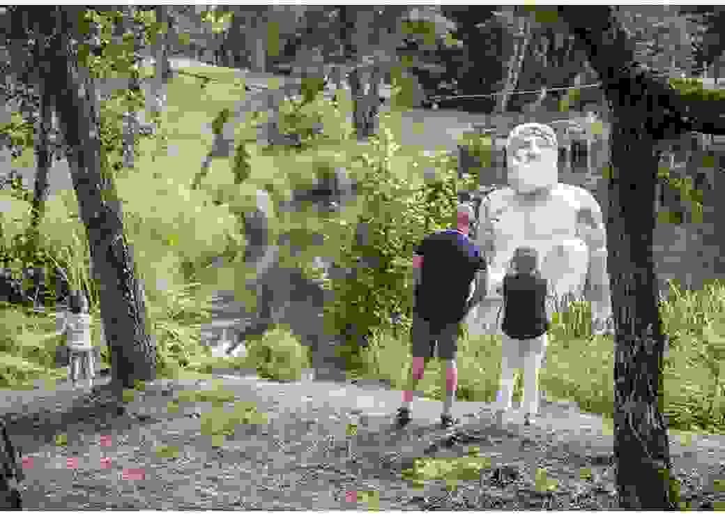 Au milieu d'un étang, une statue d'un dieu grec est installée, le bas du corps immergé dans l'eau, comme pour un bain. Depuis la berge, un couple et un enfant regardent la statue