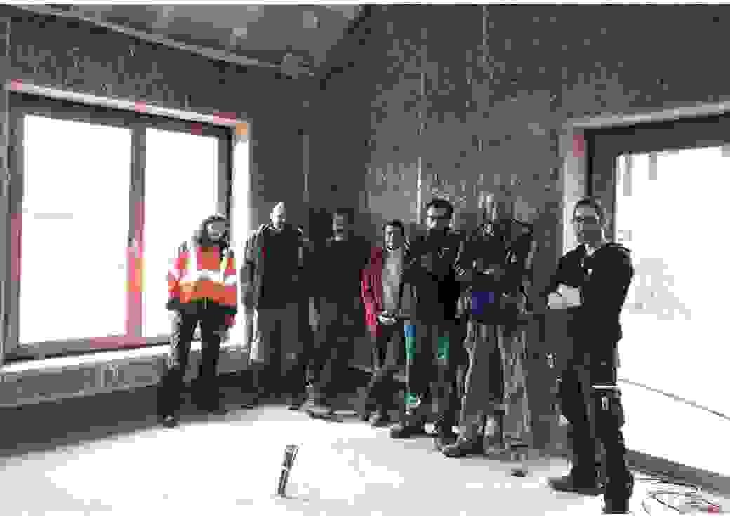 A l'intérieur d'un bâtiment dont les murs sont en paille, 7 personnes posent devant l'objectif du photographe