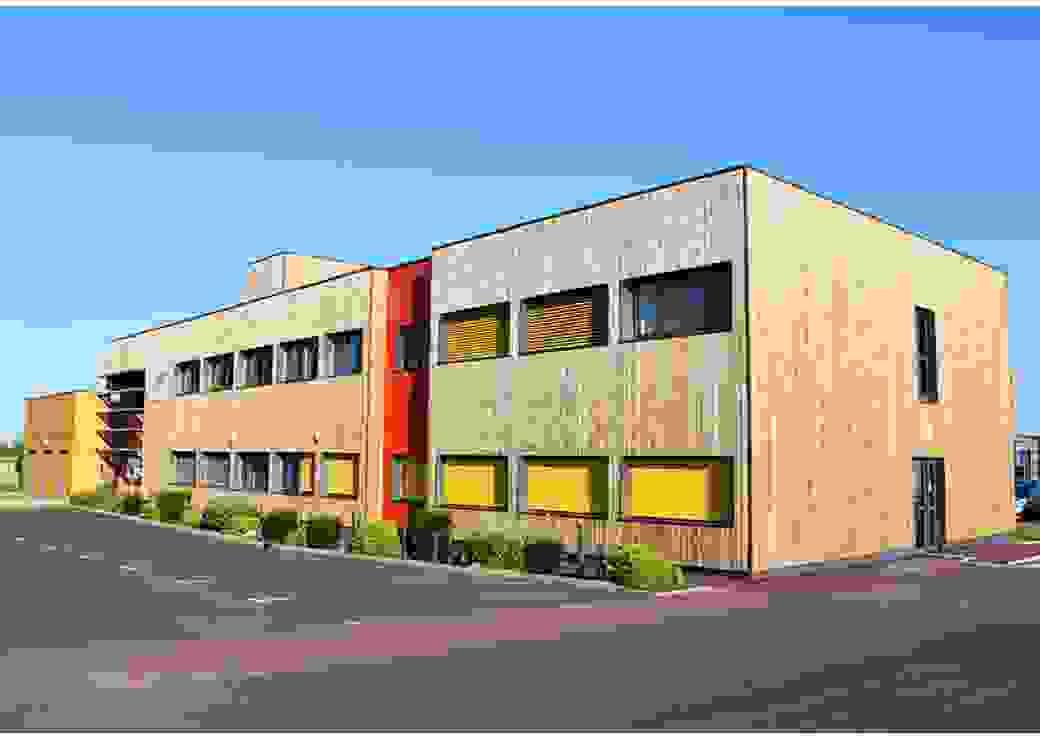 Un bâtiment, parallélépipède rectangle de 2 étages, bardé de bois doré, sur fond de ciel bleu.