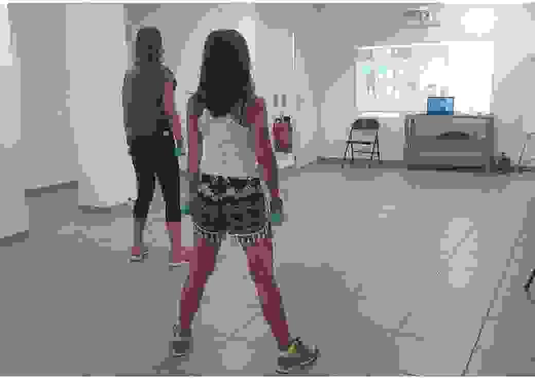Deux personnes tenant à la main des petite haltères regardent un écran