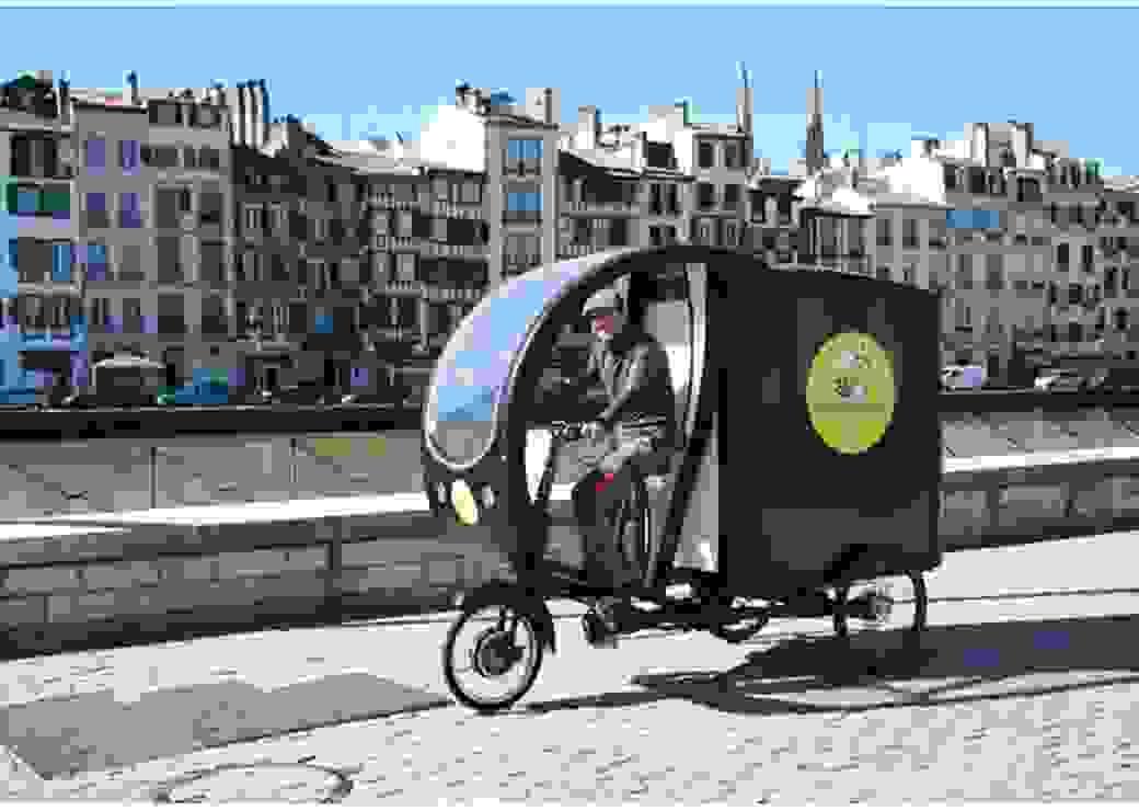 Plan large d'un vélo triporteur circulant sur les quais de Bayonne
