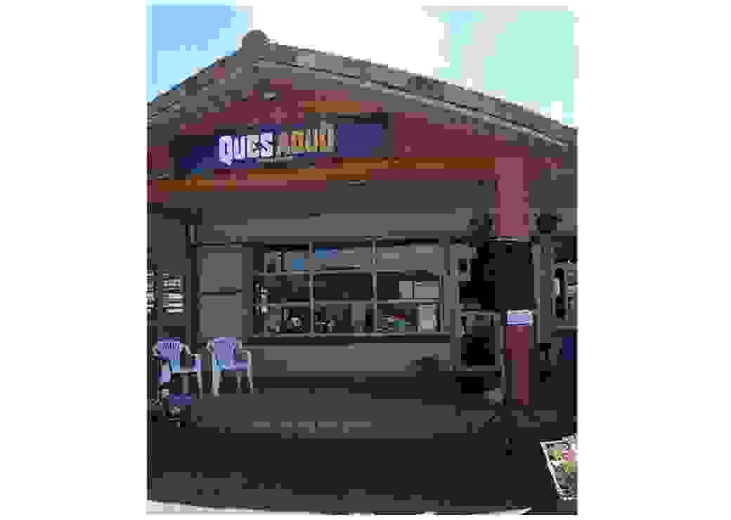 """Gros plan sur une maison qui porte une enseigne """"Quesaqyo"""". Deux chaises en plastique blanc sont disposées sur la terrasse devant le bâtiment."""