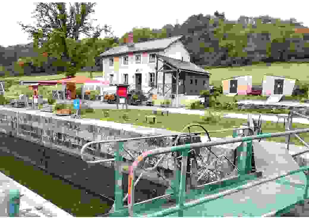 Photo de la maison de l'éclusier, prise depuis l'écluse. À droite de la maison, deux petites cabanes de bois.