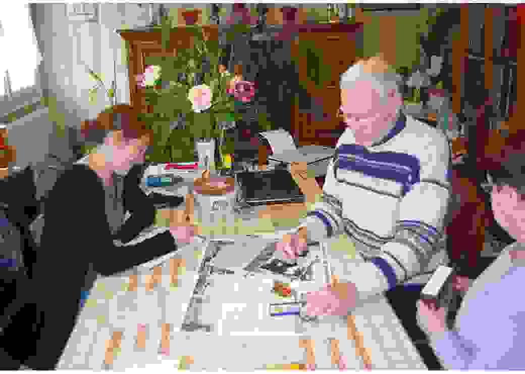 Dans le salon d'une maison, un homme et une femme âgés exposent sur la table des photos et des coupures de presse. Face à eux, une jeune femme prend des notes.