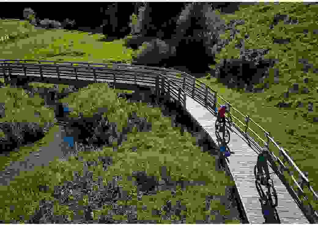 Vue aérienne montrant deux cyclistes roulant sur une passerelle de bois, au dessus d'un paysage très vert, au milieu duquel coule un ruisseau