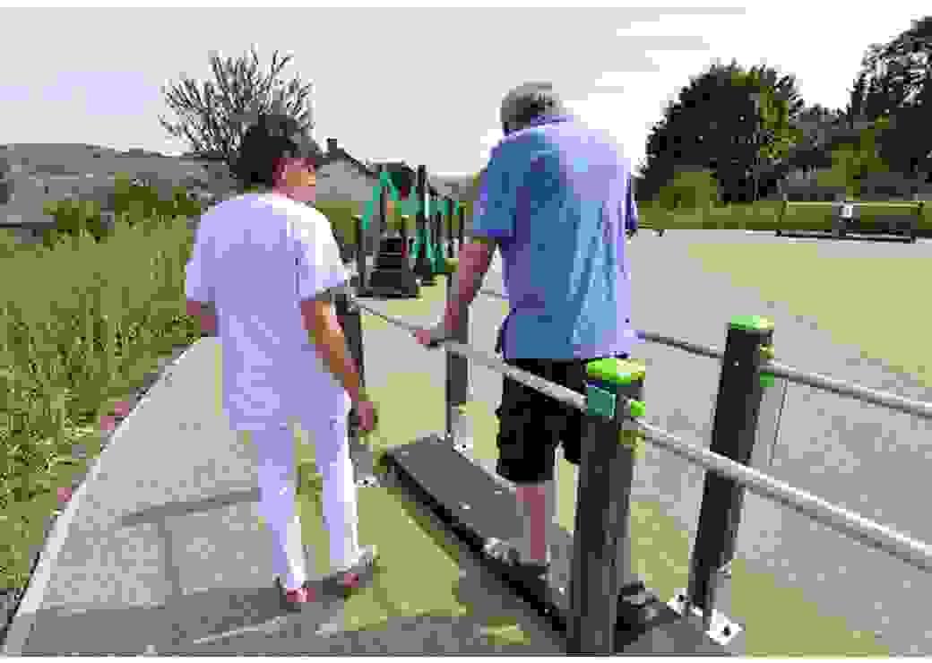 Une dame en blouse blanche accompagne un homme qui marche en se soutenant à deux barres parallèles, sur un terrain équipé d'aménagements de sport