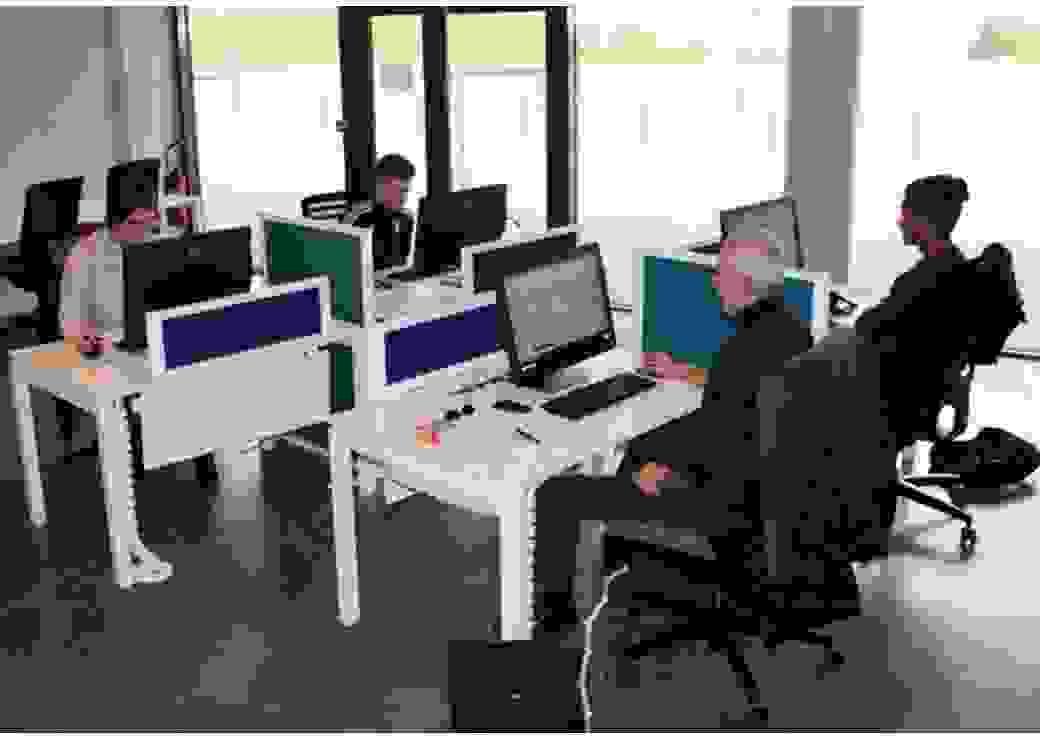 Dans une salle informatique, quatre personnes sont face à des ordinateurs