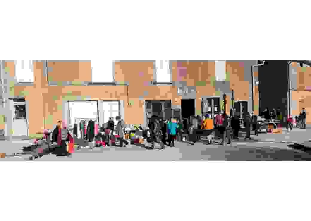 Dans une rue de village, vue panoramique d'un groupe de personnes