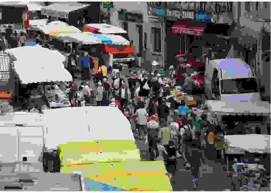 Vue d'en haut d'une rue animée par un marché, avec de la foule et les parasols des marchands