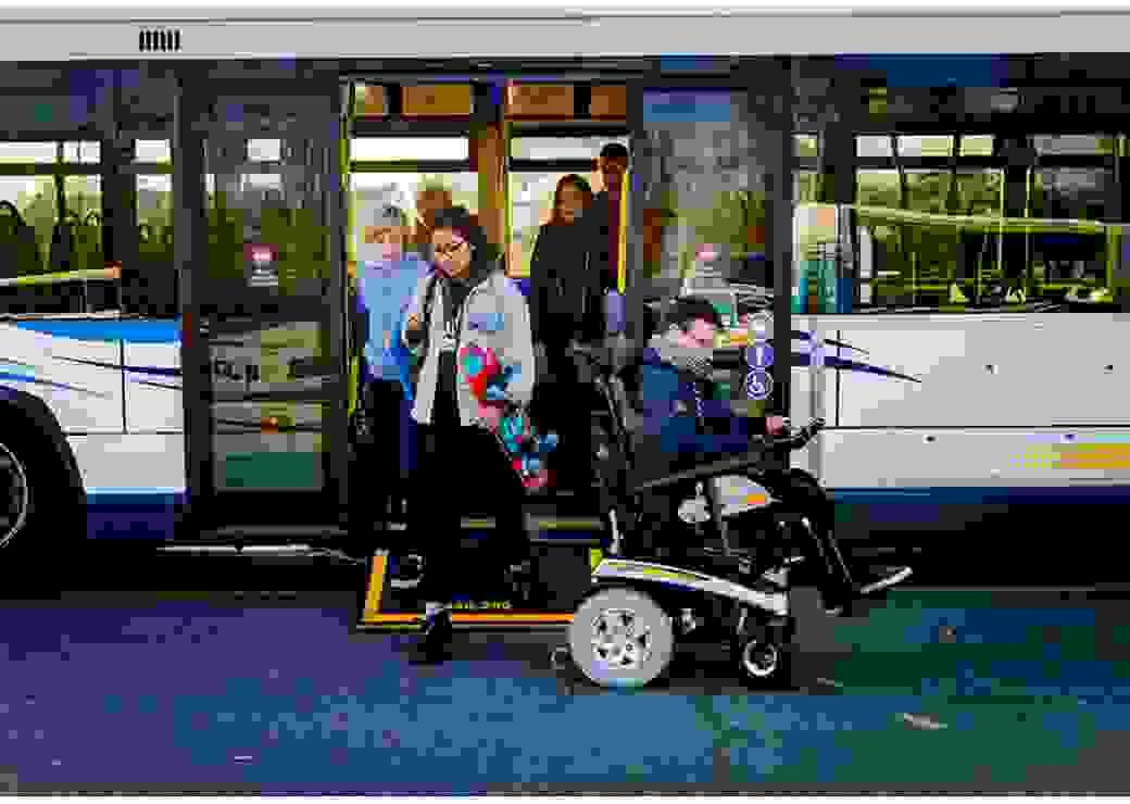 Photo d'un bus d'où descendent des personnes, dont un jeune homme en fauteuil roulant