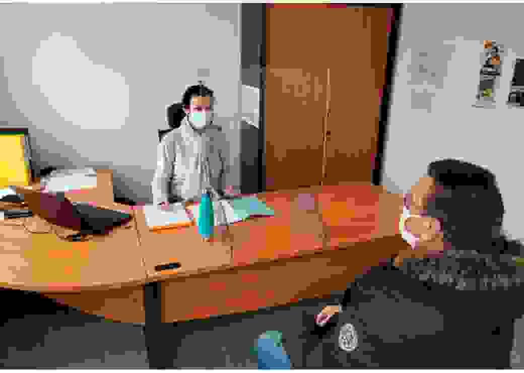 Une jeune femme assise derrière un bureau fait face à un homme assis de l'autre côté du bureau.