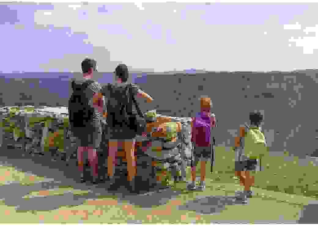 Vue de dos d'une famille au sommet d'une colline, en train de regarder le paysage du Grand Cirque de Navacelles