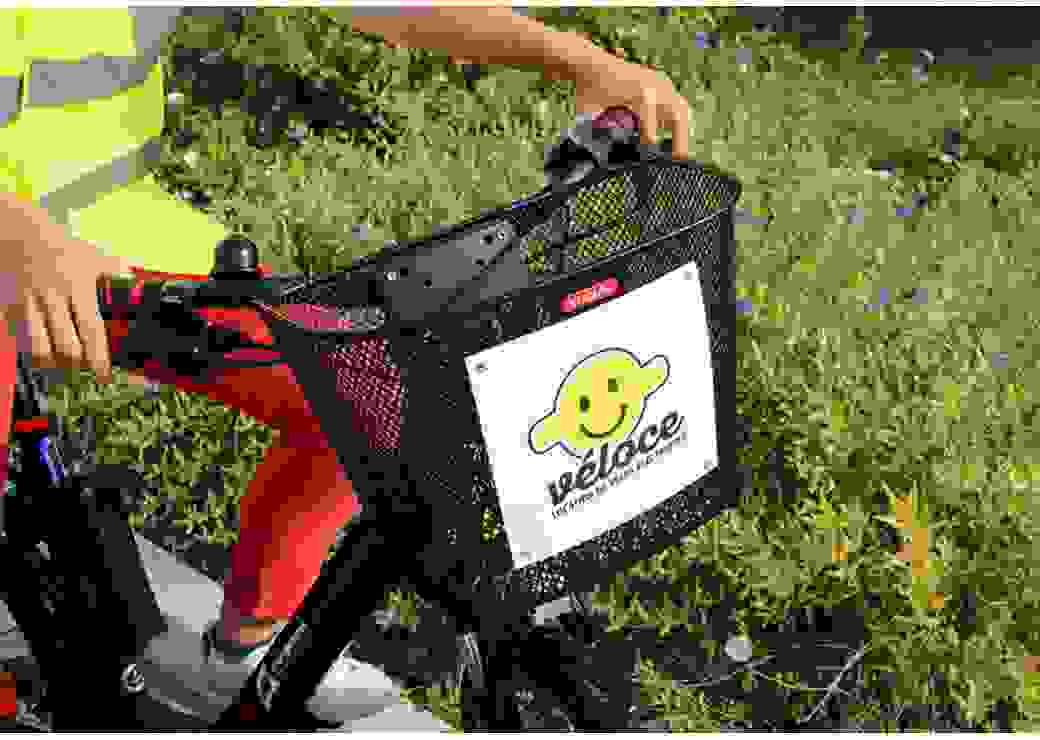 """Gros plan sur le panier accroché à un guidon de vélo. Une pancarte dit """"véloce, location de vélos électriques"""""""