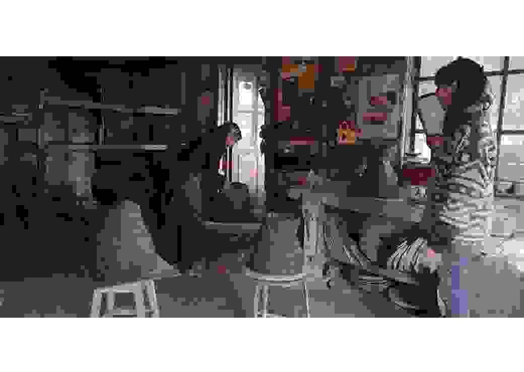À l'intérieur d'un atelier, deux femmes travaillent à des sculptures de terre cure