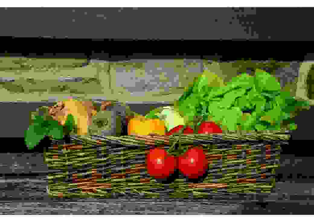 Photographie type nature morte, d'un panier en osier contenant des légumes