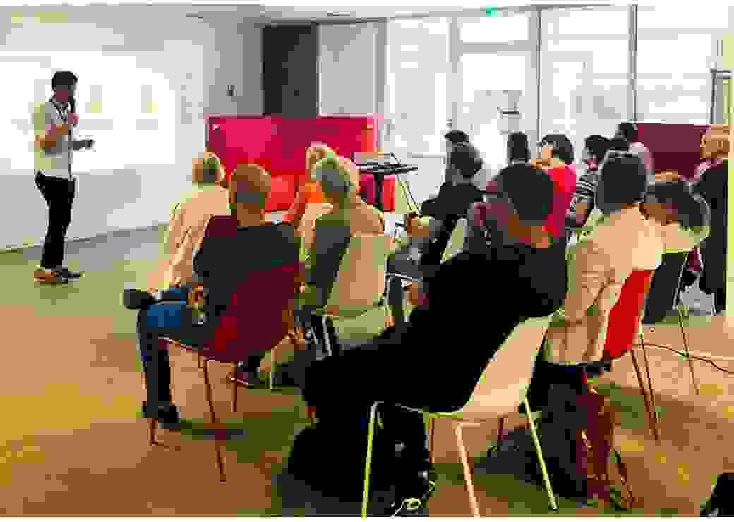 Dans une salle, des personnes assises écoute un homme qui parle au micro, devant une projection de graphiques