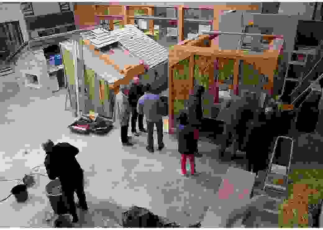 Vue de haut d'un très grand atelier où des personnes regardent des modèles de construction en bois et en paille