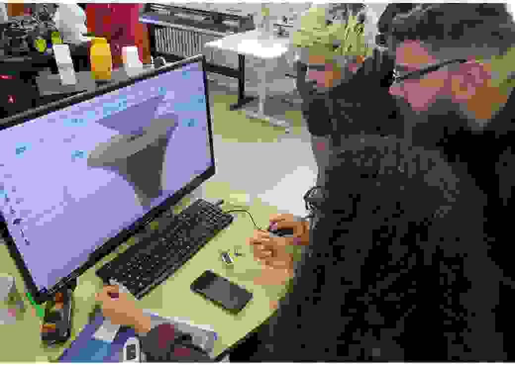 Trois personnes regardent un graphique en 3D sur un écran d'ordinateur