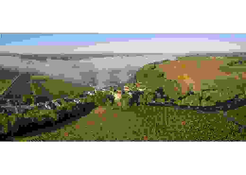 Vue aérienne panoramique d'un paysage vallonné, où l'on distingue des vignes et un village