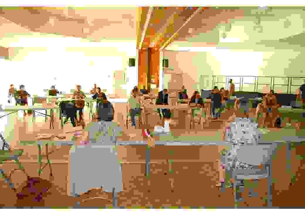 Dans une très grande salle, des personnes sont assises à des tables disposées en un grand cercle