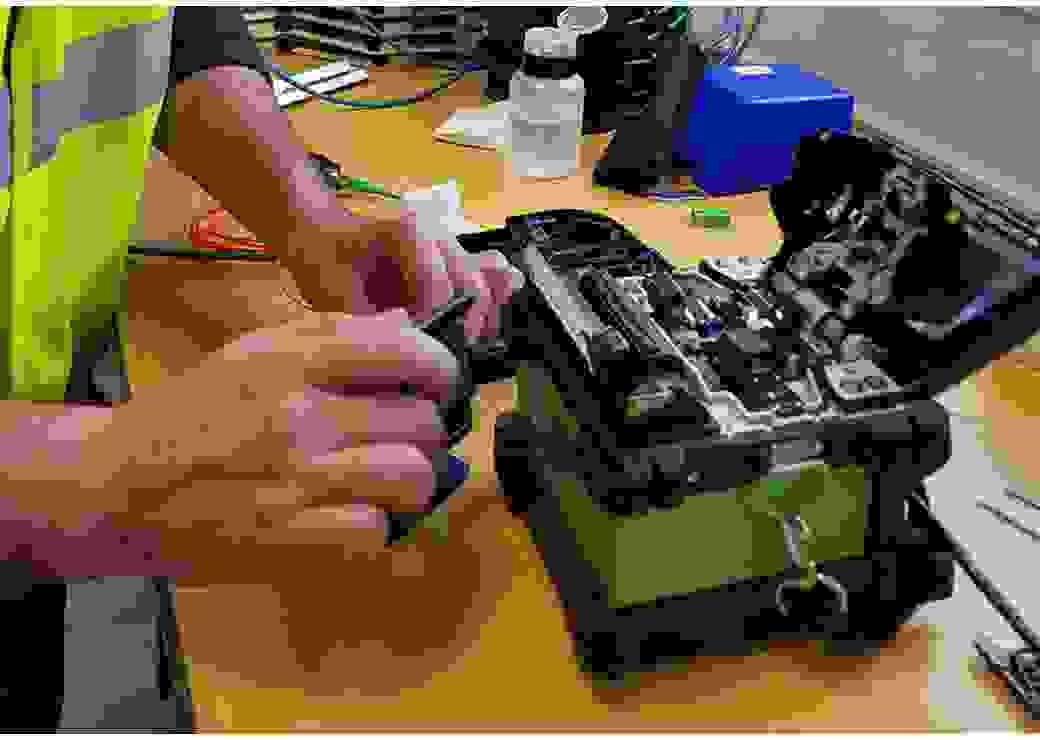 gros plan sur les mains d'un homme intervenant sur une petite mallette qui emplie de matériel électronique