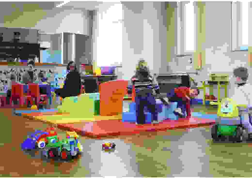 Dans une salle éclairée par trois fenêtres, des enfants en bas âge jouent sur des tapis colorés, sous la surveillance de 2 adultes