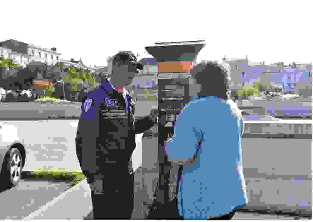Un policier municipal en uniforme et une dame parlent devant une borne de parcmètre