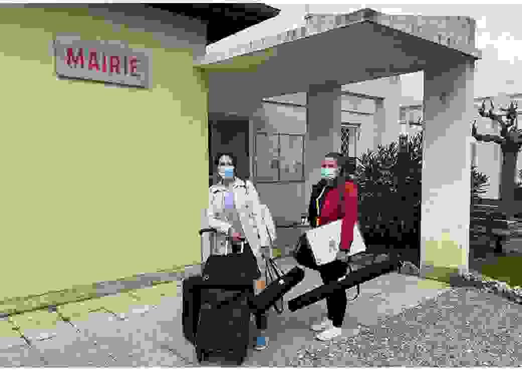 """Devant un bâtiment affichant un panneau """"mairie"""", deux femmes chargées de bagages posent pour le photographe"""