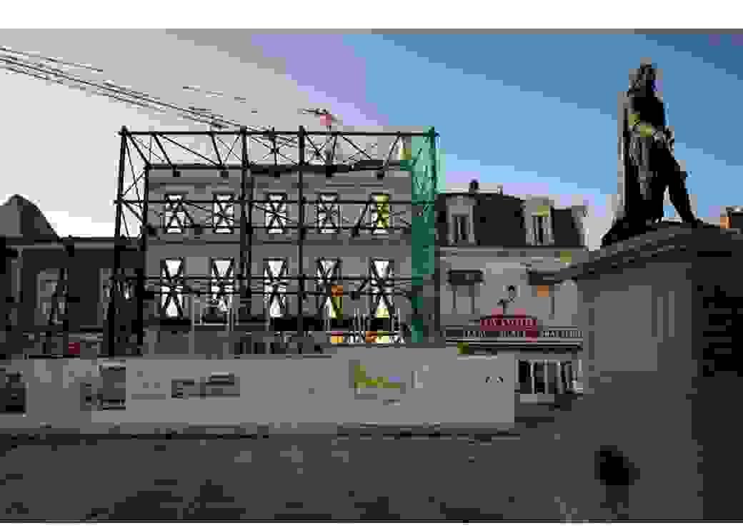 Plan large d'une place urbaine, avec une statue à droite et au centre un échafaudage