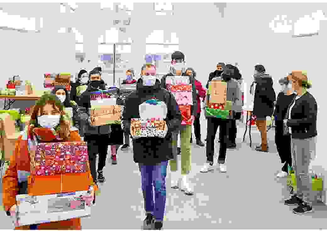 dans une grande salle, des personnes avancent face caméra, les bras chargés de paquets cadeaux