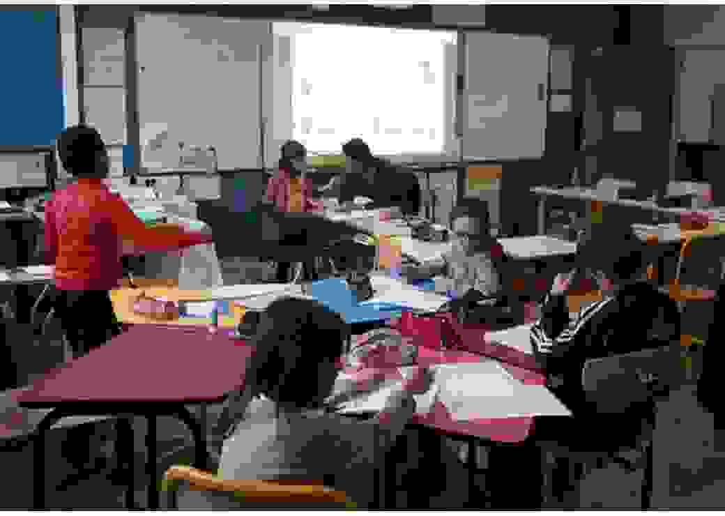La photo montre une classe où les tables sont installées en étoile, avec des enfants en mouvement