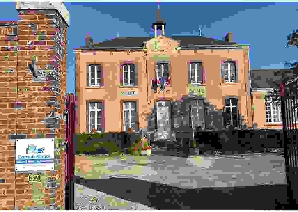 """Photo plan large d'un bâtiment de deux étages, en façade duquel on peut lire """"mairie, RF, école"""". Sur l'une des piles du portail que l'on devine dans l'encadrement de la photo, on peut """"consult station, cabinet médical connecté"""""""